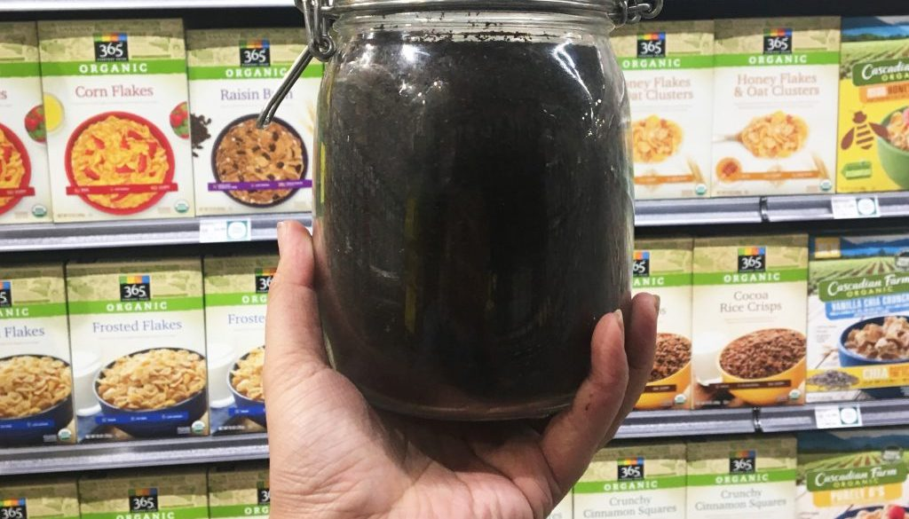 freshly ground coffee in a glass jear in front of cereal boxes at the grocery store.